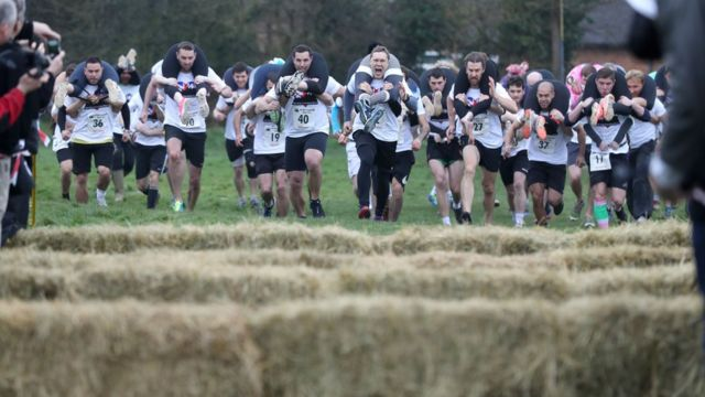 Competitors make their way off the start line as they take part in the annual UK Wife Carrying Race