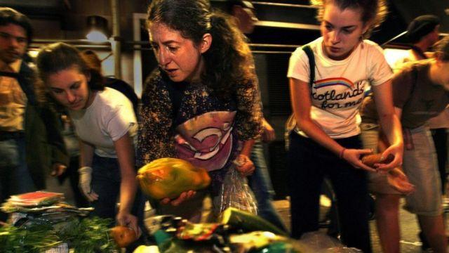 Personas recogiendo alimentos de entre la basura