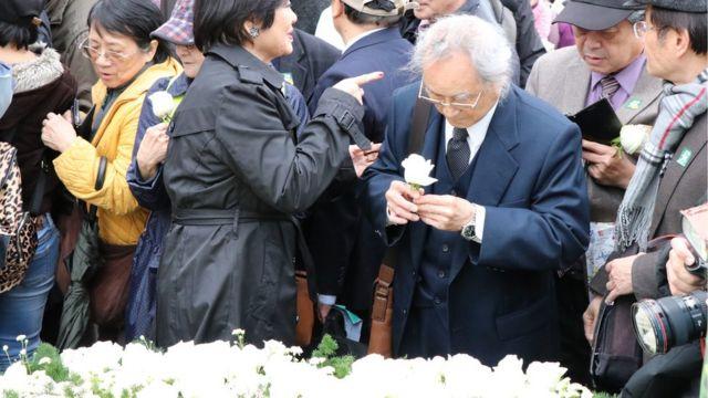 中樞紀念儀式結束後,許多民眾排隊獻花,還有人低頭啜泣。