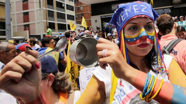 Una manifestante hace sonar una pequeza cacerola