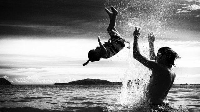 Отец и дочь играют в воде на побережье Таиланда