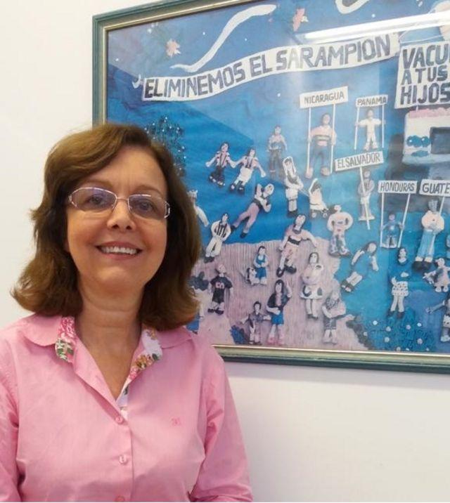 Marilda Siqueira em frente a quadro da campanha contra sarampo dos anos 90 que fica em sua sala