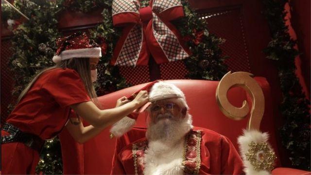 Mulher ajeita homem vestido de Papai Noel usando viseira de plástico