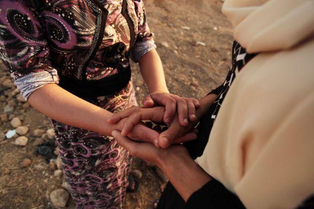 Shaima and Laila hold hands