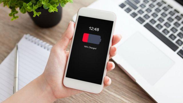 Mão segura celular com notificação de pouca bateria