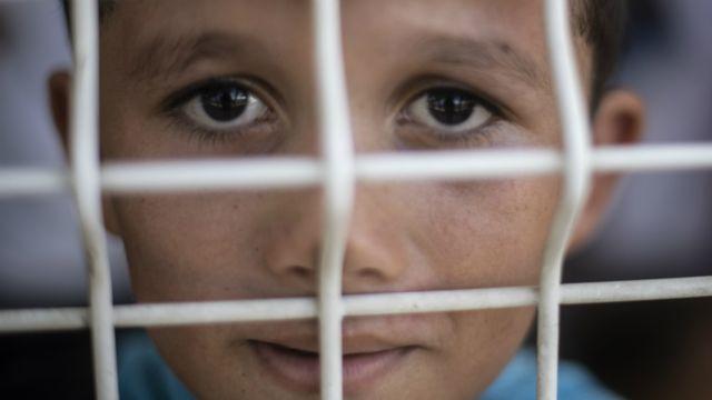 Niño migrante detrás de rejas