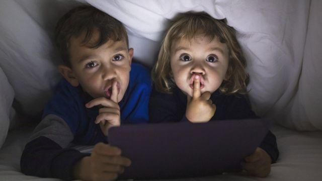 Duas crianças fazendo gesto de silêncio