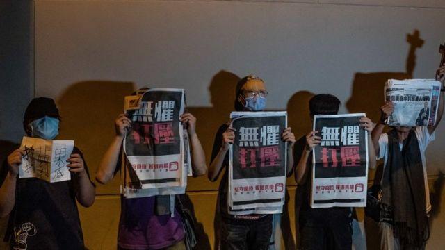 """Activistas prodemocracia mostrando ejemplares del diario de Lai """"Apple Daily""""."""