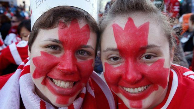 Personas con la bandera de Canadá pintada en sus rostros.