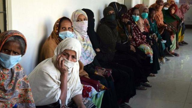 Warga Pakistan antre untuk menerima bantuan dalam pandemi Covid-19.