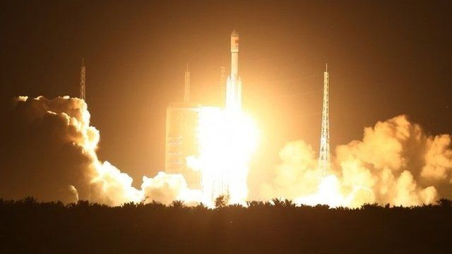 "Spectators watch as a Long March 7 (CZ-7) rocket lifts off the launch pad in Wenchang in southern China""s Hainan Province"