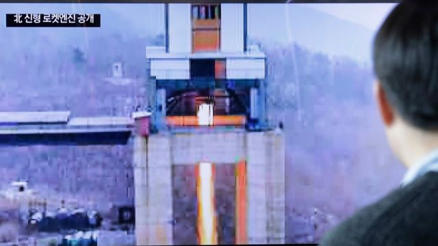 """A man watches a TV news program showing an image that North Korea""""s Rodong Sinmun newspaper reports of a ground test of a new type of high-thrust rocket engine at Seoul Railway station in Seoul, South Korea, Sunday, March 19, 2017"""