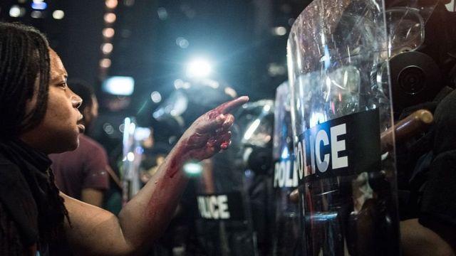 """Manifestante del movimiento """"Black Lives Matter"""", frente a agentes de policía."""