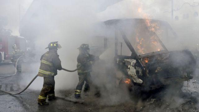 Bomberos apagan incendio en autobuses.