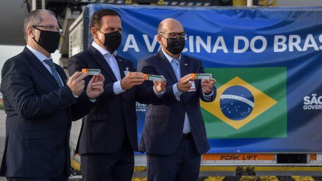 El gobernador de Sao Paulo, Joao Doria, el secretario de salud de Sao Paulo, Dr. Jean Gorinchteyn, y el director del Instituto Butantan, Dimas Covas, junto a un contenedor con dosis de CoronaVac en el aeropuerto de Sao Paulo.