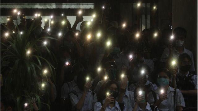 学生们打开手机闪光灯表示抗议。