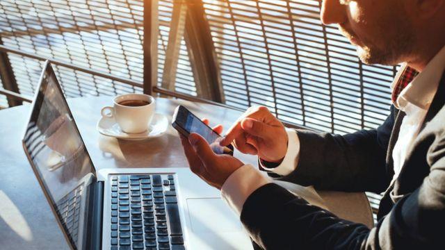 شخص يمسك بهاتفه المحمول الذي يعمل باللمس بينما يجلس أمام جهاز الكمبيوتر المحمول