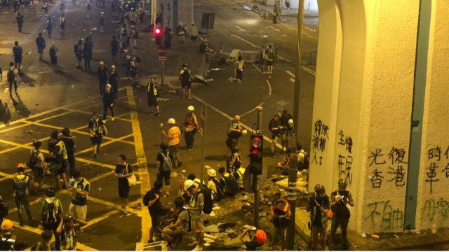 示威者纷纷撤退,留下墙上的涂鸦,满地狼藉,远处的警察仍然站在那里待命。