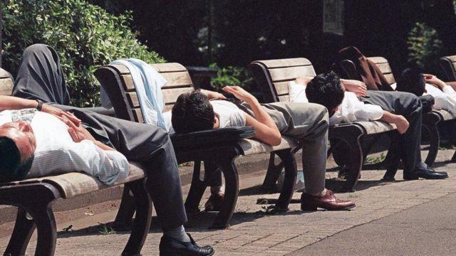 Homens japoneses deitados em bancos de praça