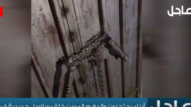 صورة من المقطع تظهر السلاسل التي أُغلق بها الباب