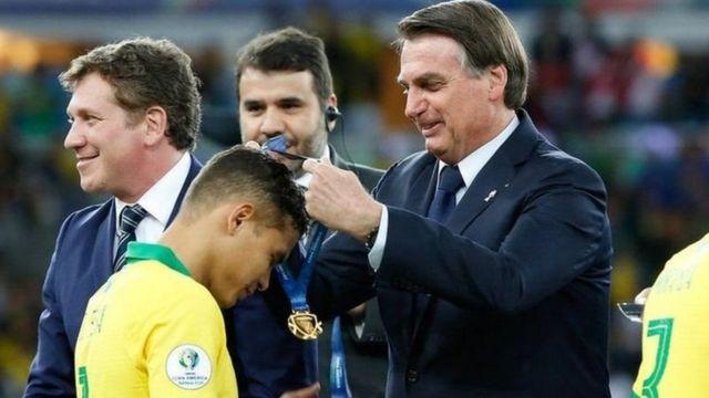 Brezilya Devlet Başkanı Jair Bolsonaro, 2019'da Copa America'yı kazanan milli takım oyuncularına madalyalarını takıyor