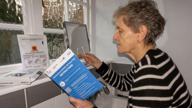 Anh: Một phụ nữ sử dụng bộ tự xét nghiệm Covid-19 tại nhà