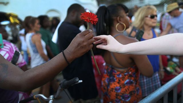 Dos brazos se extienden para compartir una flor