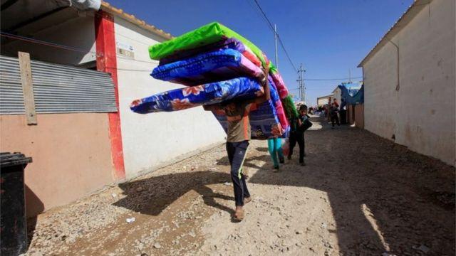 イルビルの北西にある収容施設で支援物資を受け取ったモスルからの避難民(20日)