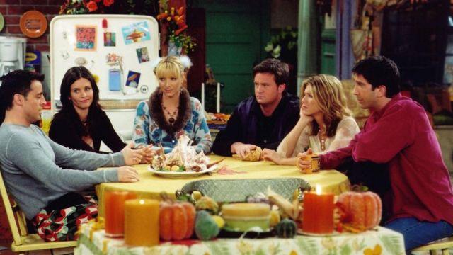 Cena do seriado Friends, com os seis personagens principais sentados em uma mesa no Dia de Ação de Graças