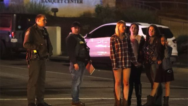 Young girls stand by police