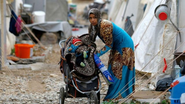 A Syrian refugee mother puts her baby into a stroller in Nizip refugee camp, near the Turkish-Syrian border in Gaziantep province, Turkey, 30 November, 2016.
