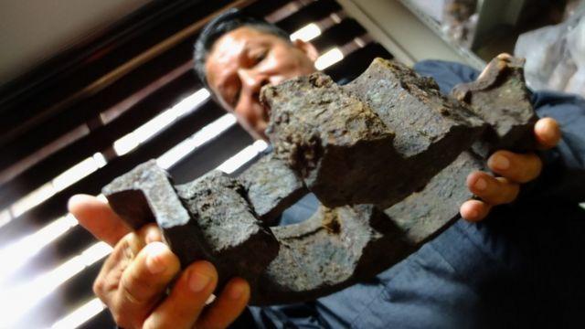 Eddy Becerra muestra los restos de una antigua rueda que se desplazaba por los rieles del ingenio al puerto.