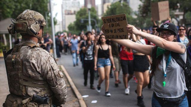 Manifestantes y militar en Chile