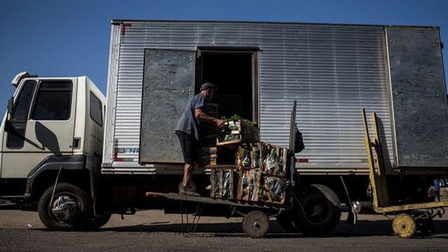 Caminhão sendo abastecido com hortaliças