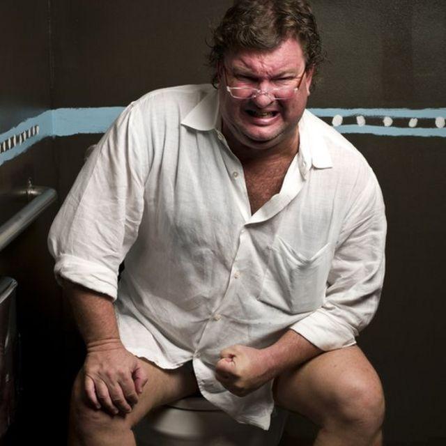 مردی نشسته روی کاسه توالت در حال زور زدن