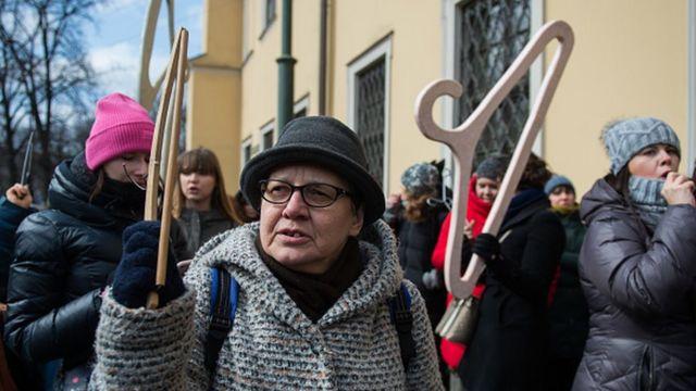Mujer sostiene una percha en manifestación sobre el aborto.
