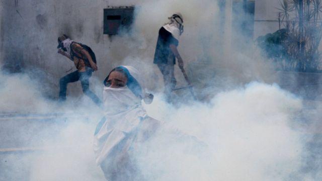 Manifestantes envueltos en una nube blanca de gas lacrimógeno en Caracas, Venezuela
