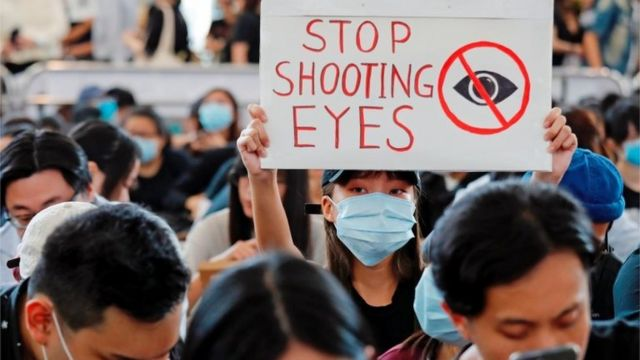 """A protester in the airport holds a sign that says """"stop shooting eyes"""""""