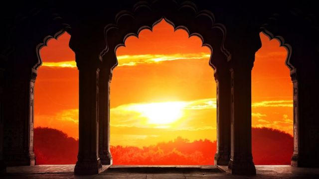 Indian arch silhouette in old temple at dramatic orange sunset sky background.