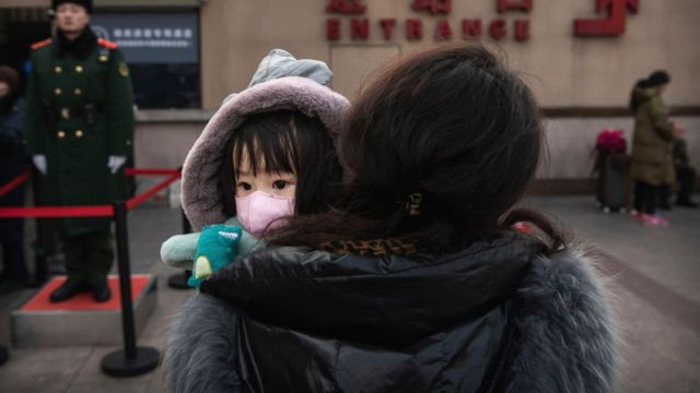 A Chinese girl wears a protective mask as she is held by a relative as they wait to board a train at Beijing Railway station