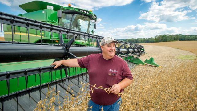 美国马里兰州农民站在大豆收割机旁