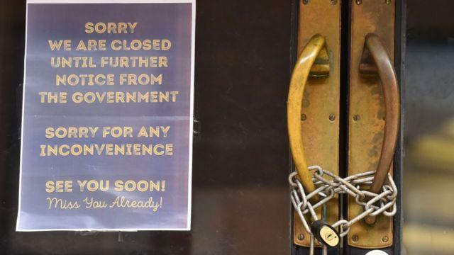 Uma loja fechada a cadeado exibe uma placa dizendo 'desculpe, estamos fechados até novo aviso do governo, desculpe por qualquer inconveniente, nos vemos em breve'