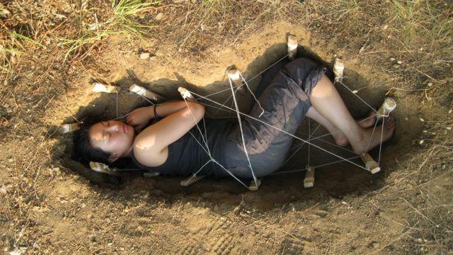 Jae Rhim acostada en la tierra reproduce una forma de entierro ecológico.