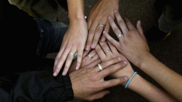 Manos de jóvenes con el mismo anillo