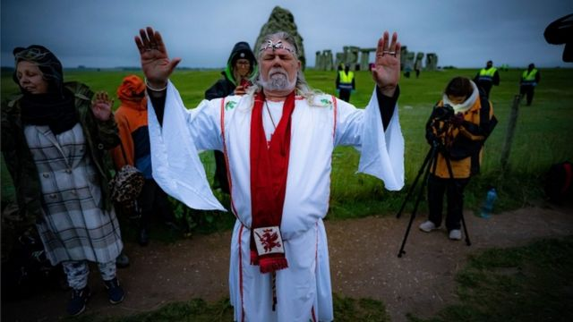 Arthur Uther Pendragon performs a ritual during summer solstice at Stonehenge, where people watch the sun rise at dawn of the longest day in the UK
