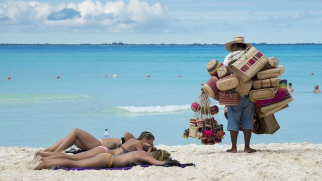 Women sunbathing on the beach while a vendor watches them in Mexico.