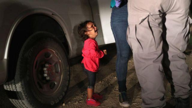 Menina de dois anos chorando enquanto sua mãe lida com agentes de segurança
