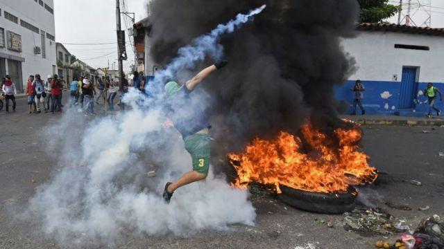 Manifestante detrás de neumáticos incendiados