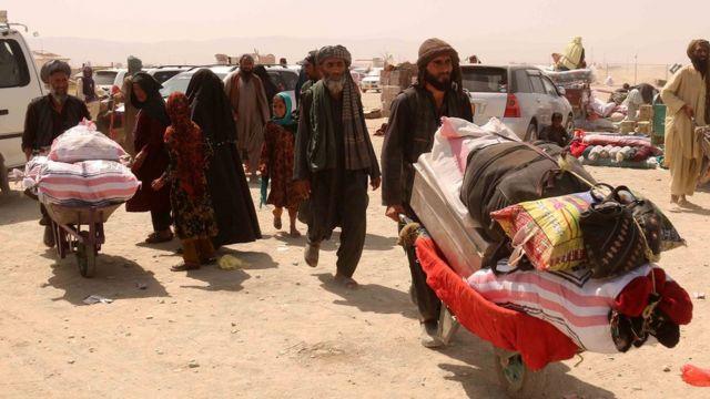 Afganos llevan sus posesiones en carretilla hasta la frontera