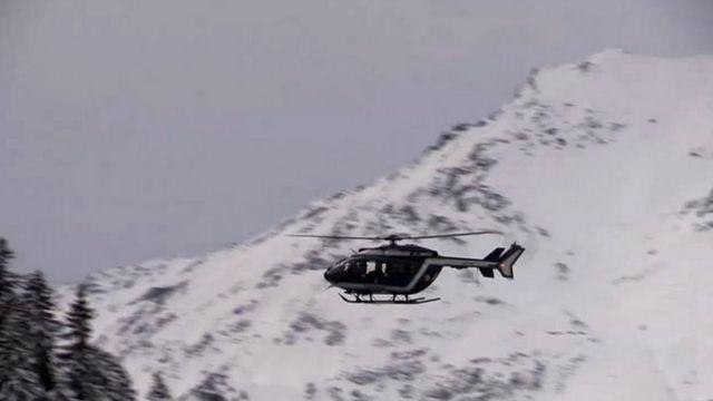 事故現場の上空を飛ぶ救助ヘリ(18日)